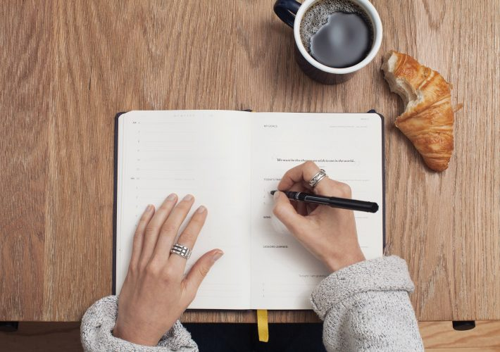 Woman in knitted sweater writes in notebook next to croissant and coffee about to dos for the day as a productivity tips for the new year