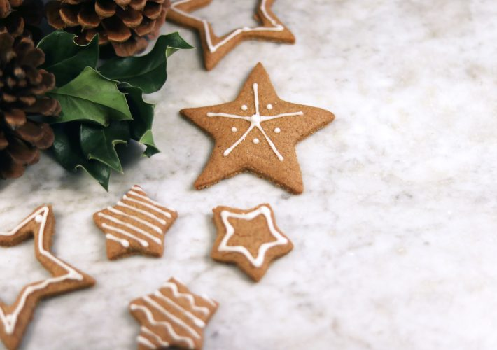 Christmas cookies, gingerbread, laid on marble counter next to Christmas plant decorations whilst people have ideas of things to do on christmas eve