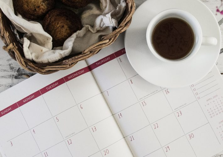 Coffee cup lies on calendar next to plant on white table as planning new years resolutions and setting goals takes place with these tips for How to Set Good New Year's Resolutions to Kick Off 2021