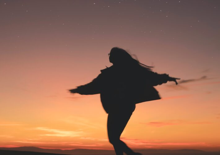 Girl with long hair and jacket dances under the moon in the evening sunset. What To Do During Moon Phases: Planning, Goals & Manifesting