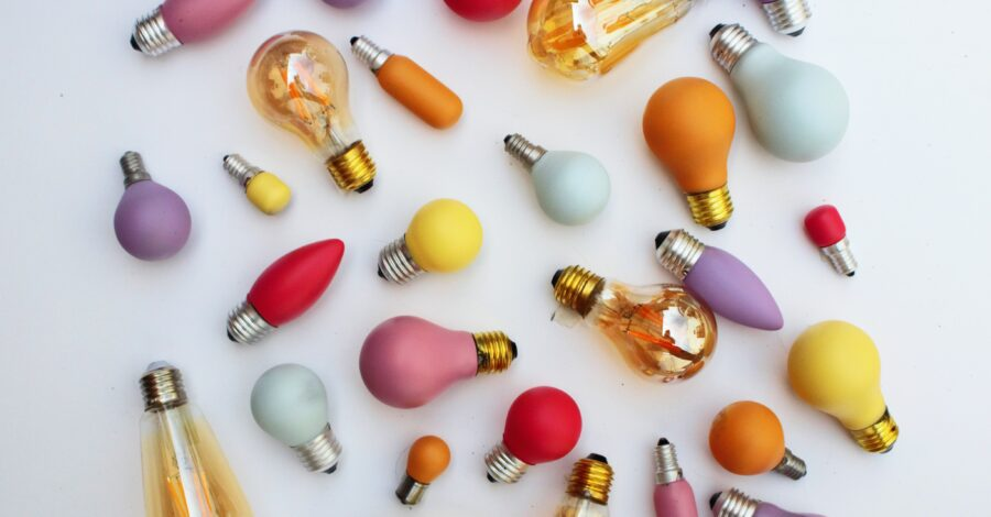 Brightly coloured blue, pink, orange and yellow light bulbs laid out in a creative, artistic way for a photo of art. Photography on a list of creative hobbies
