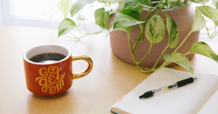A mug of coffee with an inspirational quote to help you get inspired about life sits next to a plant and an open notebook where you can plan for how to get inspired about life.