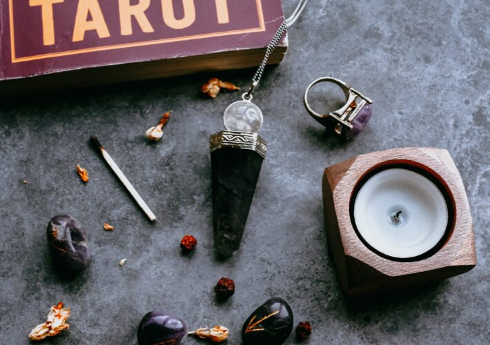 A obsidian pendant sits on a stone table next to a tarot deck, a candle and some other witchy things.
