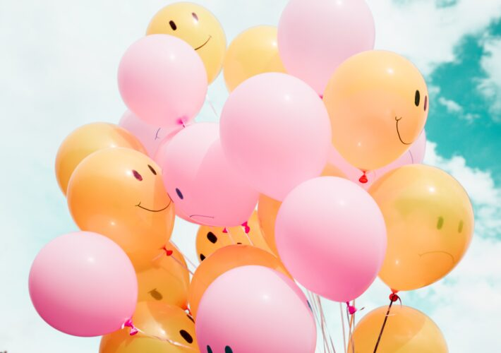 Pink and yellow balloons with smiley faces given to people so they can enjoy their life under the blue sky.