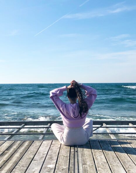 Woman in white and pink workout clothing sits on a wooden boardwalk in front of the sea to calm her anxiety with a grounding technique