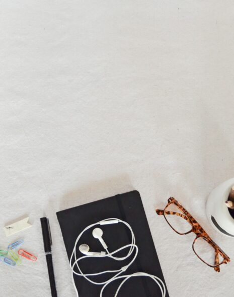 A black jorunal notebook lies on a desk next to some red glasses, a small air plant, earphones and stationary for motiving yourself to study and studying for work, for school, for your career or just for fun