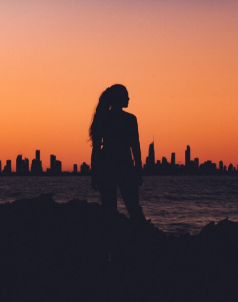 A girl stands as a silhouette infront of a sunset over a lake and city skyline thinking about how to stop being scared to act
