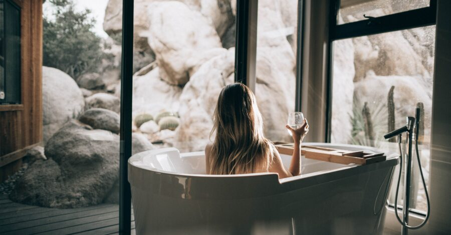 A woman sits and relaxes in a bathtub with a glass of wine and stares out of the windows at the nature outside as she thinks about how to stop rushing through life