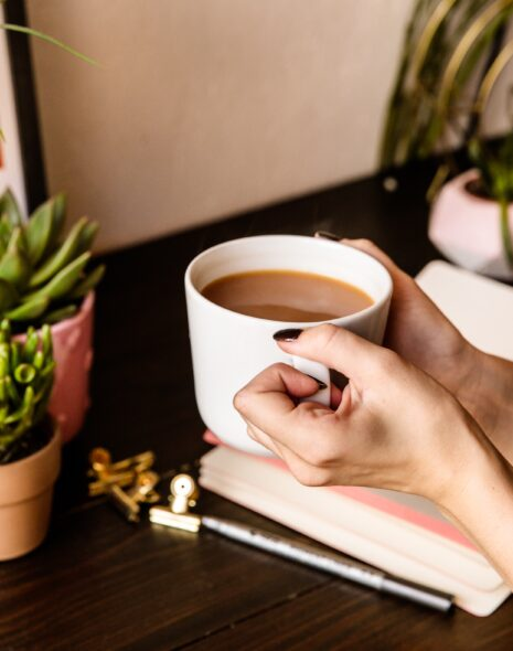 A journal lies open on a desk with a girl drinking coffee surrounded by spring time flowers, some paint samples and stationary. Journal for spring journal ideas and journal prompts for growth.