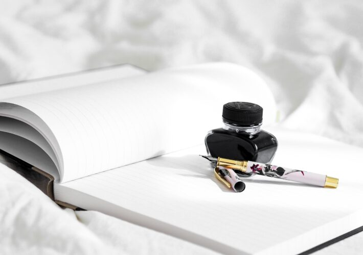An ink pot and quill sit on an open notepad on a white duvet on a bed, ready for write even when you don't want to and how to beat writer's block