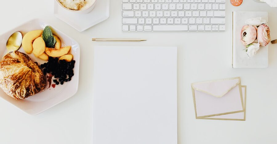 Someone uses tips on how to be self-motivated, by writing out a plan for their goals on a piece of paper and learning to take action. A keyboard sits next to stationary and a bowl of fruit on a white desk.