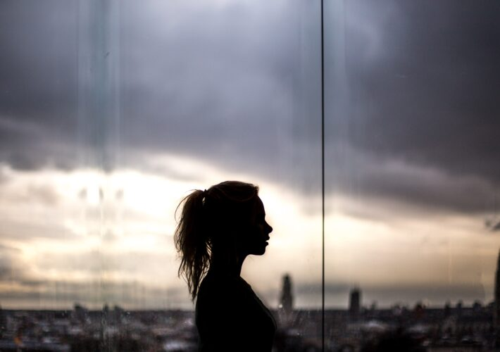 A shadow silhouette stands in front of a purple, cloudy sky outside as a girl things about how to do shadow work