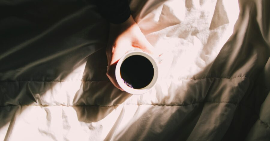 A cup of coffee on bed sheets, in the morning sunrise light as part of the best daily routine for healthy life choices