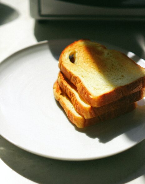 Start your morning off right with these slices of toast piled up on a plate in the morning sun ready to begin the day as part of a morning routine.