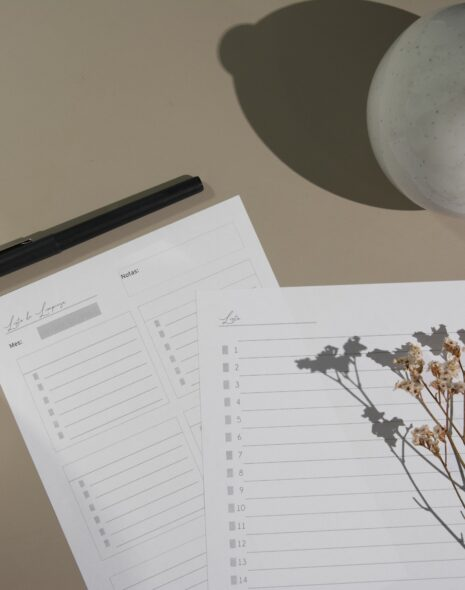Writing lists and plans for preparing for the new academic year for uni prep and study inspo. A beige table has a white and black coffee mug with two lists and some pressed flowers.
