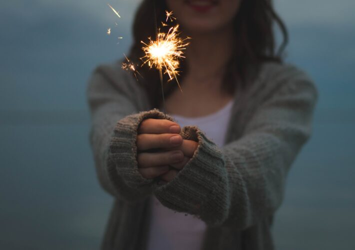 A girl stands with a sparkler for motivation and inspirational quotes