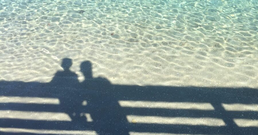 A parent and a child stand on a pier and look out over the blue sea water together with a strong relationship where the child knows how to get along with his parents.